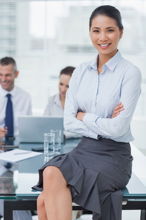 Smiling businesswoman in bright office posing with workmates on background photo