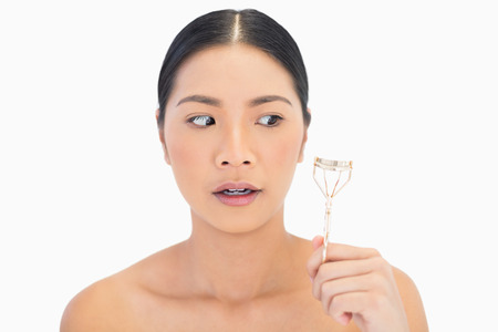 Apprehensive natural model holding eyelash curler on white background photo