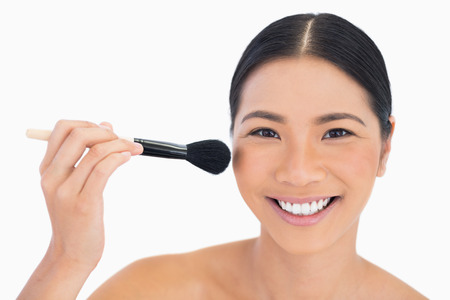 Cheerful dark haired woman applying powder on her face on white background photo
