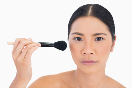 Serious dark haired woman applying powder on her face on white background photo