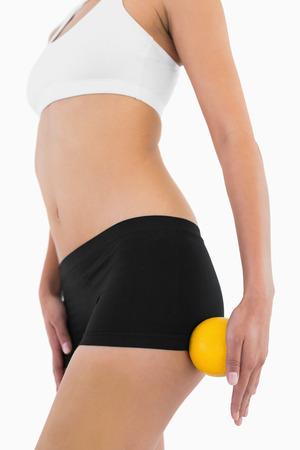 with orange and white body: Carrocer�a delgada femenina con la ropa interior deportiva celebraci�n de naranja sobre fondo blanco