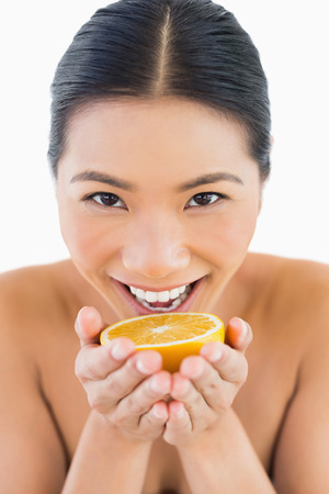 Cheerful pretty woman holding orange slice in her hands on white background photo