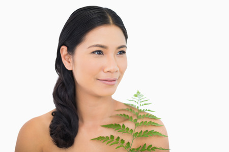 dark haired woman: Relaxed dark haired woman with fern on white background