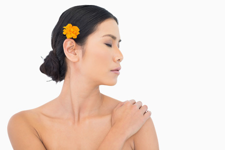 Pensive model with orange flower in hair touching her shoulder on white background photo