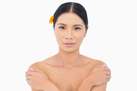 Sensual model with orange flower in hair touching her shoulders on white background photo