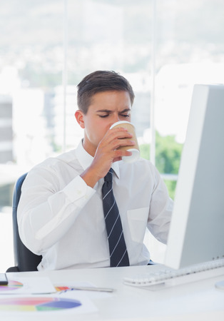 Young businessman drinking coffee at his desk at work photo