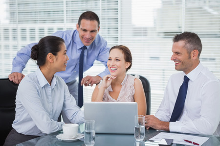 Cheerful colleagues around laptop working together in bright office photo
