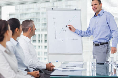 Businessman analyzing graph during presentation in bright office photo