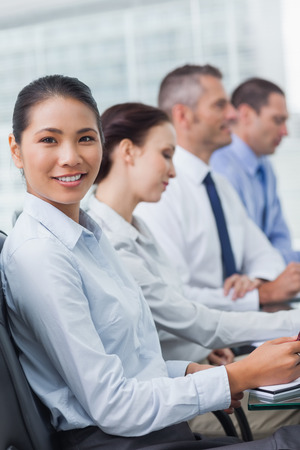 Cheerful employee attending presentation with her colleagues in bright office photo