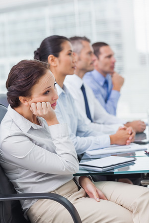 Bored businesswoman attending presentation in bright office photo