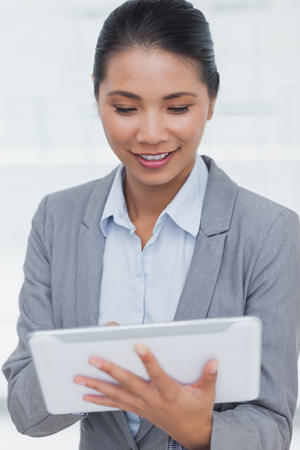 scrolling: Happy businesswoman in bright office posing scrolling on her tablet pc