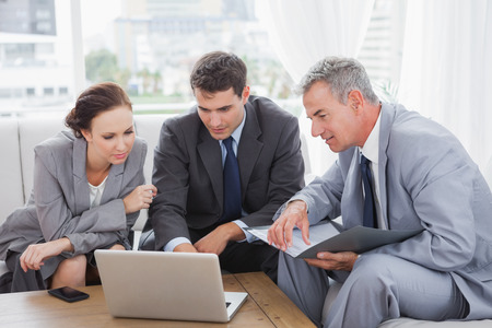 Business people working together on their laptop in cosy meeting room Stock Photo