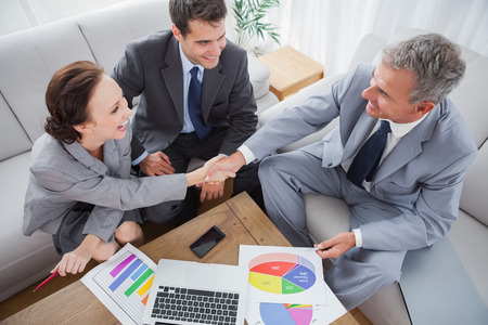 Business people shaking hands while working in cosy meeting room photo