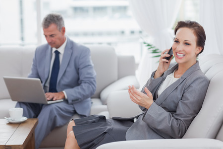 Businesswoman calling while her colleague working on his laptop in bright office photo