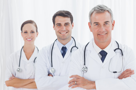 health service: Smiling doctors posing together in bright office