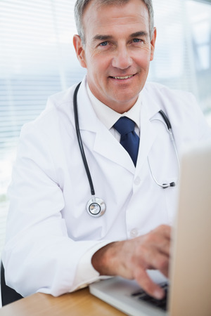 Smiling experienced doctor typing on his laptop in bright office photo