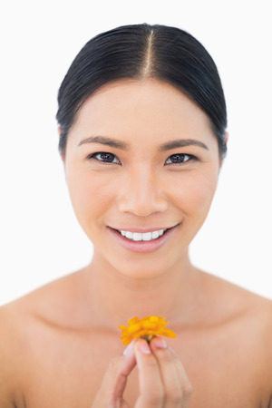 Smiling natural black haired model holding orange coloured flower on white background photo