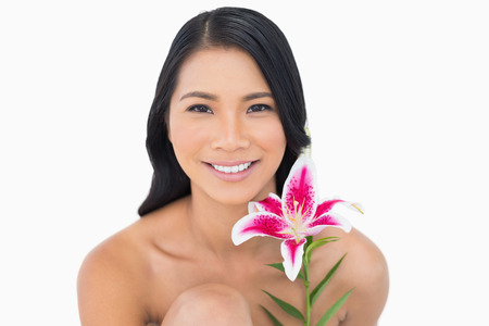 Smiling natural black haired model posing with lily on white background photo