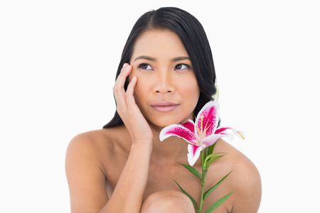 Natural model posing with lily and touching her face on white background photo