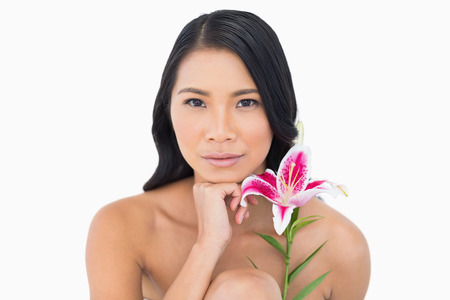 Natural model with lily touching her chin on white background photo