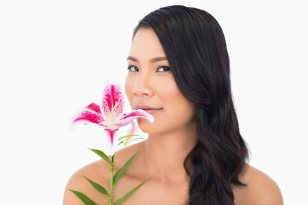 Peaceful natural brown haired model smelling lily on white background photo