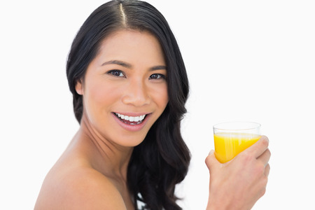 Cheerful sensual  model with glass of orange juice on white background photo