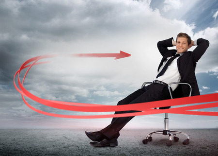 Businessman sitting with red arrow going past him smiling at camera in swivel chair photo