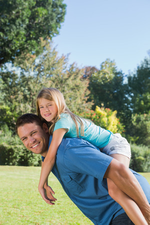 Daughter getting piggy back from dad smiling at camera in the park on a sunny day photo