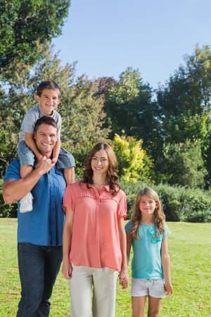 Young family with two children posing in a park smiling at camera photo