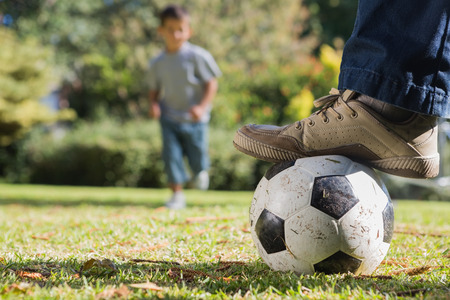 Child running for the football under his fathers foot in the park photo
