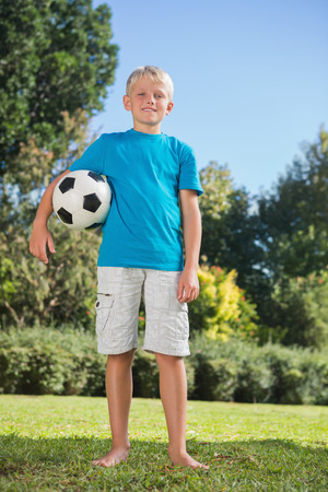 Young blonde boy holding football in the park smiling at camera photo