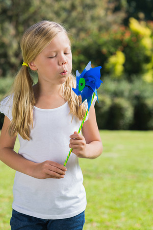 Young blonde girl blowing pinwheel in the park on sunny day photo