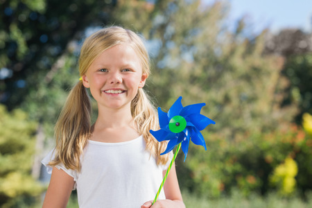 Young blonde girl holding pinwheel smiling at camera in the park on sunny day photo
