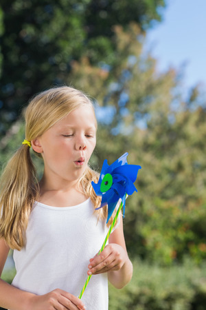 Small child blowing the pinwheel on summers day in the park photo