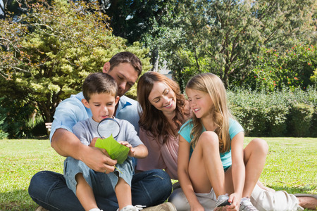 Happy family in a park with father and son inspecting leaf with magnifying glass on summers day photo