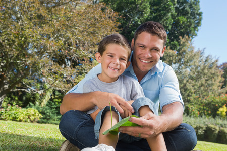 Smiling dad and son holding a leaf in a park looking at camera photo