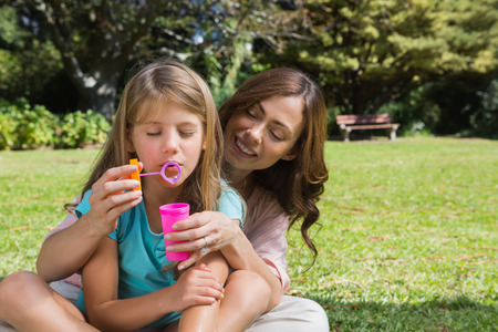 Mother and daughter enjoying making bubbles in the park photo