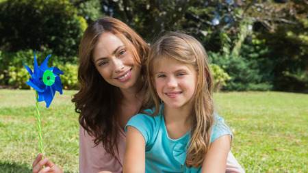 Happy mother and daughter holding pinwheel smiling at camera in the park photo