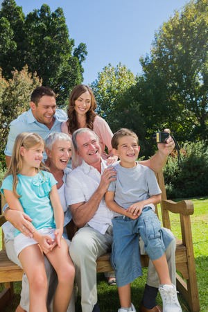 Multi generation family sitting on a bench taking photo of themselves in the park photo