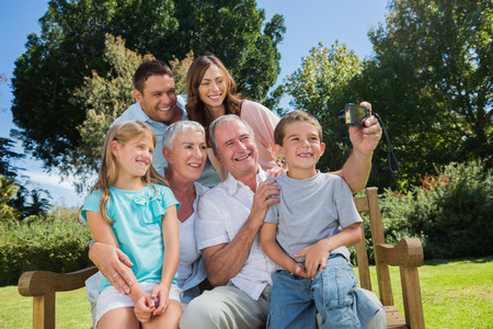 Multi generation family sitting on a bench taking photo of themselves photo