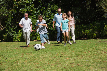 Happy multi generation family playing football together in the park photo