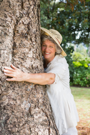 Retired woman hugging a tree and smiling in a park