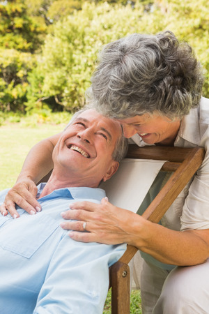 Happy mature woman smiling and embracing her husband on a deck chair photo