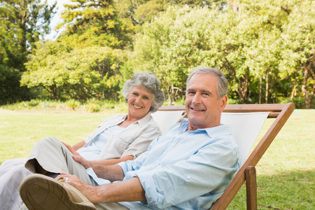 Happy mature couple sitting on sun loungers in park looking at camera photo