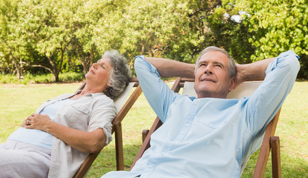 Relaxing mature couple sitting on sun loungers in the park in sunshine photo