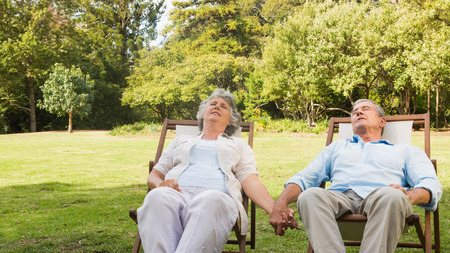 Mature couple relaxing on sun loungers on a sunny day photo