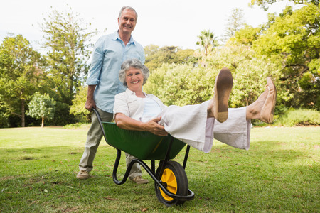 Cheerful man pushing his wife in a wheelbarrow and smiling at camera photo