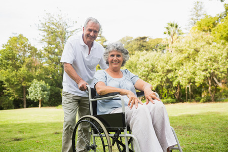 Mature woman in wheelchair with partner smiling at camera at the park