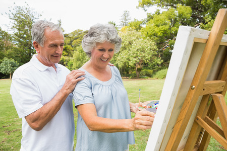 Content retired woman painting on canvas and talking with husband in the park on sunny day photo