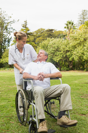 Happy man sitting in a wheelchair talking with his nurse pushing him at the park on sunny day photo